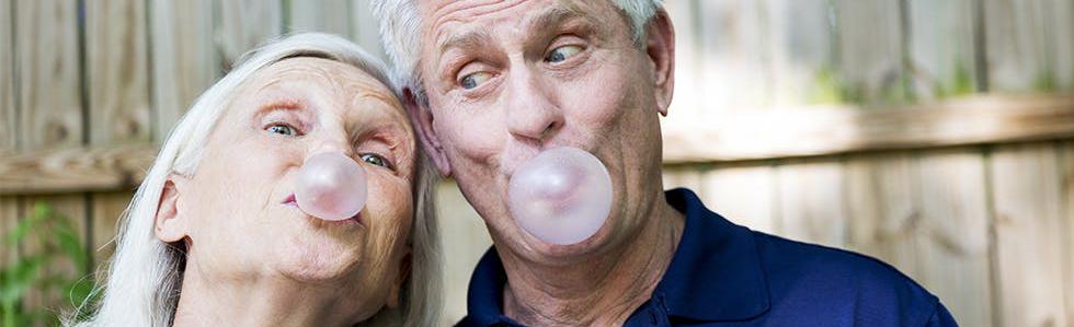 Kvinne og mann som blåser bobler med tyggis. Foto.