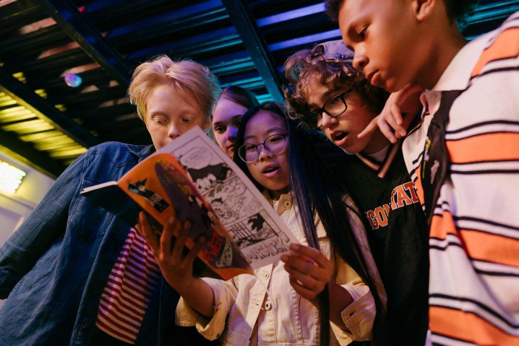En gruppe med barn som ser på samme tegneseriebok
