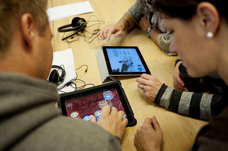 3 studenter bøyd over to iPads.