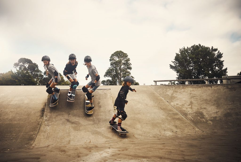 Critical movement literacy  Four boys on skateboards racing down a ramp.