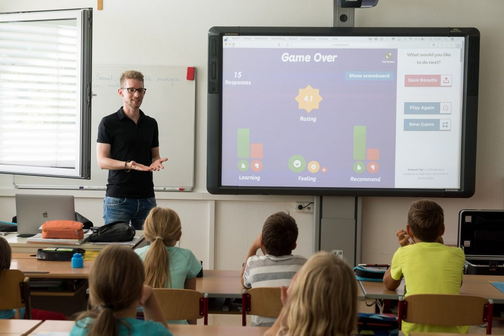 Teaching health skills   A teacher standing in front of a school class, with a Kahoot on the board.