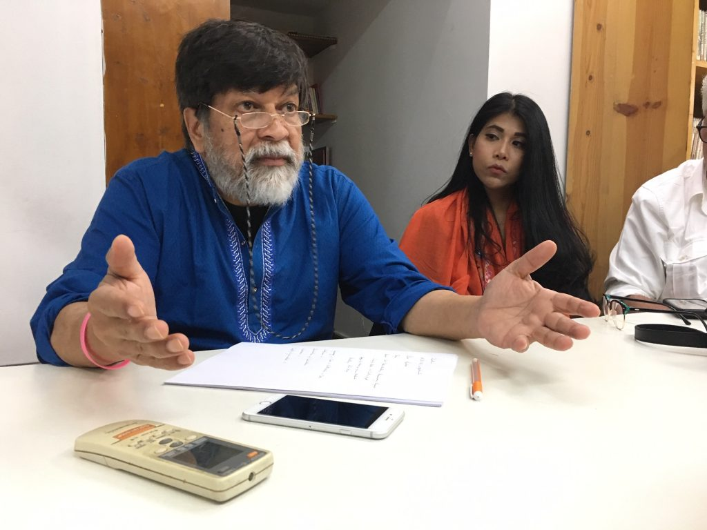 Shahidul Alam talking with a table