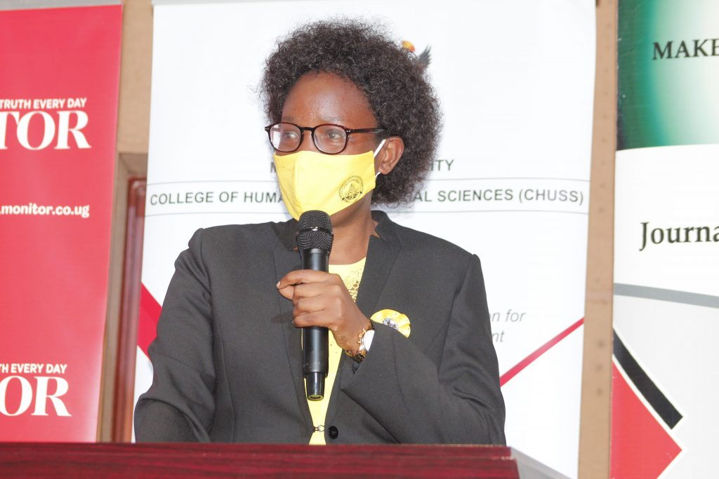 speaking on a podium wearing a mask