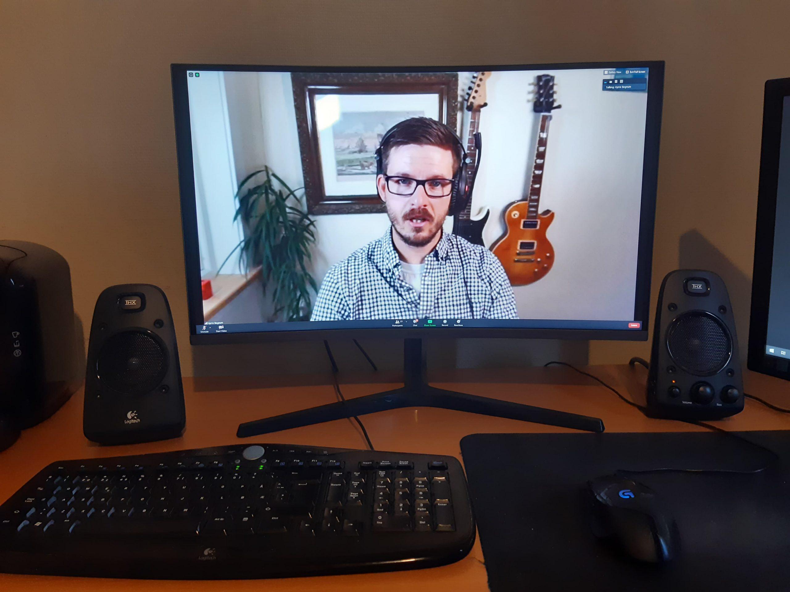 Bilde av et skrivebord med PC-skjermer. Kyrre underviser fra en av skjermene