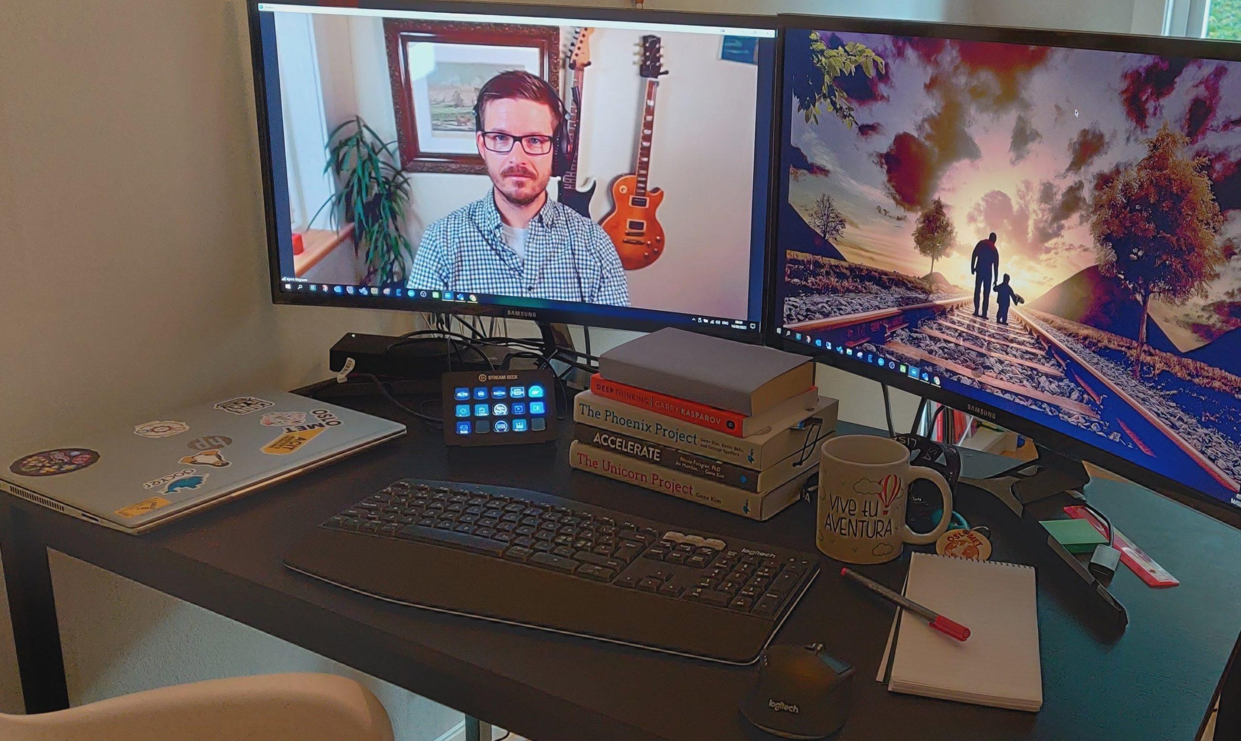 Bilde av et skrivebord med PC-skjermer. Kyrre underviser fra en av skjermene.
