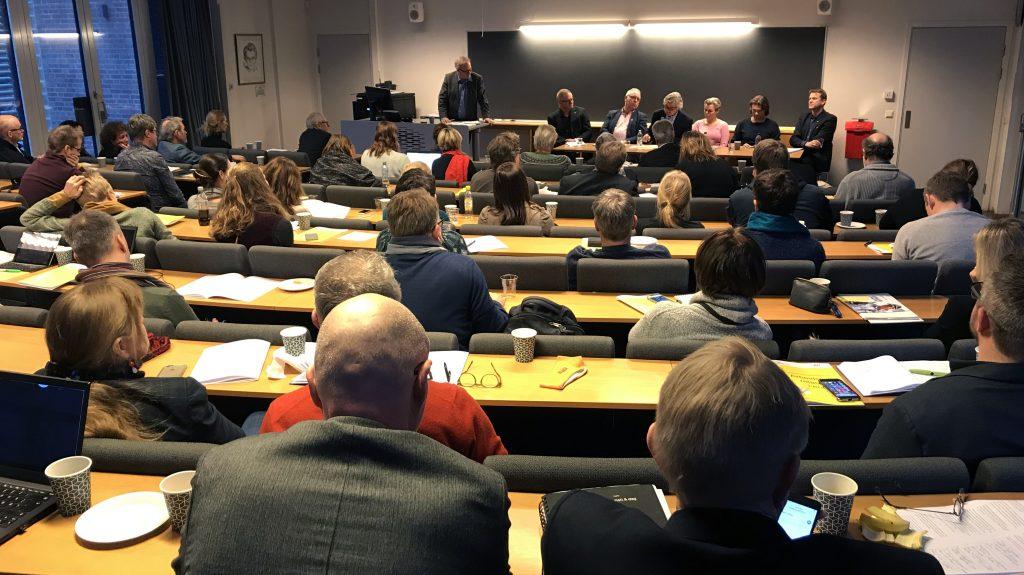 Bilde av et fullsatt auditorium, med panelet som diskuterer årets resultater i front.