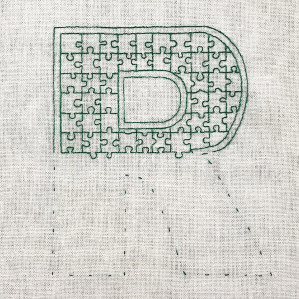 Motiv brodert med attersting i puslespillmønster, bokstaven R.