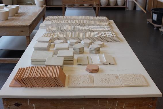 Viser stabler av rå og råbrente keramiske fliser samlet på et bord