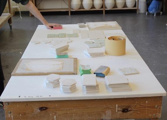 Viser råbrente keramiske fliser på et bord som blir pusset med sandpapir.