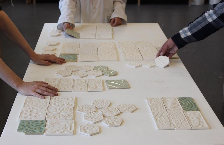 Bildet viser hendene til tre personer som står rundt et brod med et utvalg av keramiske fliser.