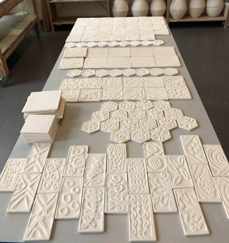 Viser bord fylt med råbrente keramikk fliser med ulik tekstur og mønster.
