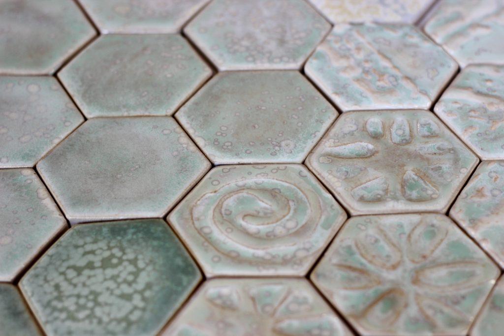 Viser nærbilde av 6 kantede fliser med ulike mønster i overflaten og grønnfarge.