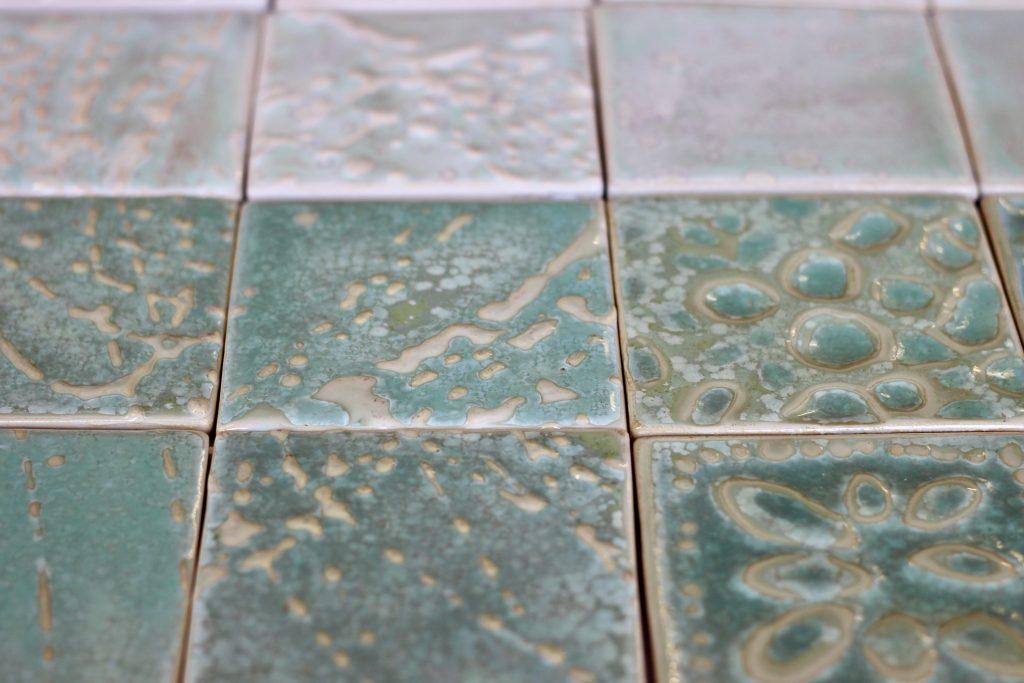 Viser nærbilde av 9 kvadratiske fliser som har ulike mønster og grønnfarger.