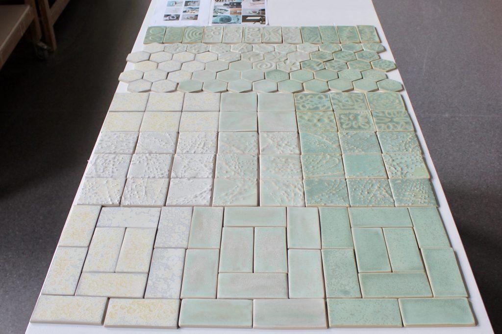 Viser en forfalte der keramiske fliser i ulike størrelser, farge og form er lagt utover for å vise hvordan flisene skal monteres sammen.