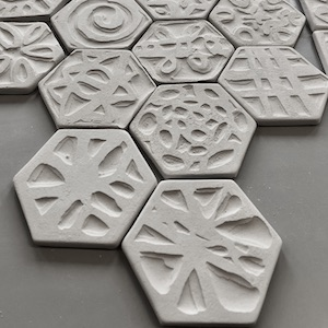 Keramiske fliser, hvite, 6 kantede, mønster, relieff i overflaten.