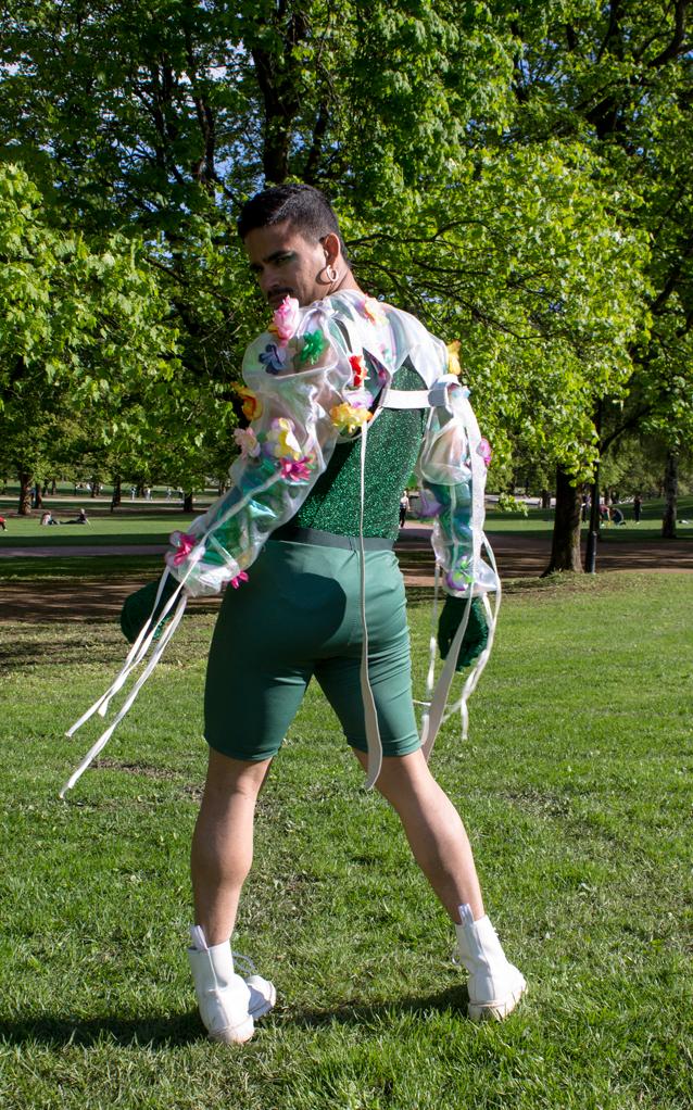 Mann ser inn i kamera med ryggen til. Grønne klær som glitrer.