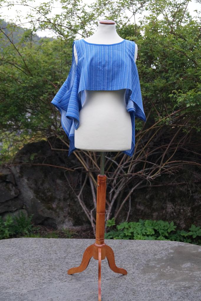 Framsiden av en blå overdel med hvite striper. Henger på en byste som overdelen draperes på.