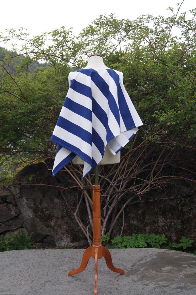 Baksiden av en blå og hvit overdel med brede striper. Henger på en byste som overdelen draperes på.