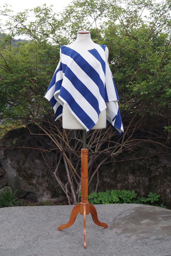 Framsiden av en blå og hvit overdel med brede striper. Henger på en byste som overdelen draperes på.