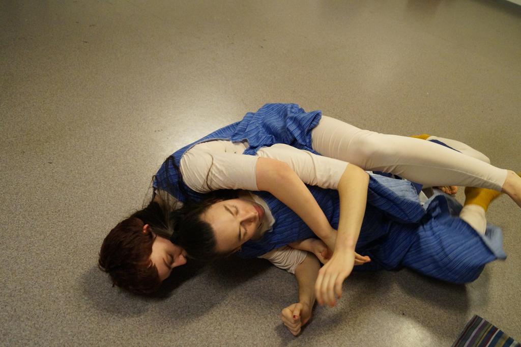 To dansere ligger på gulvet i samme kostymet.