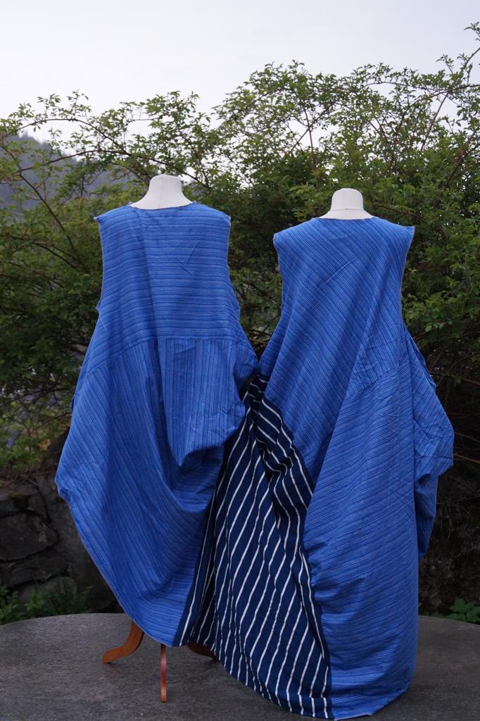 Baksiden på kjole for to personer. To ulike blåstripede stoffer. Henger på to byster.