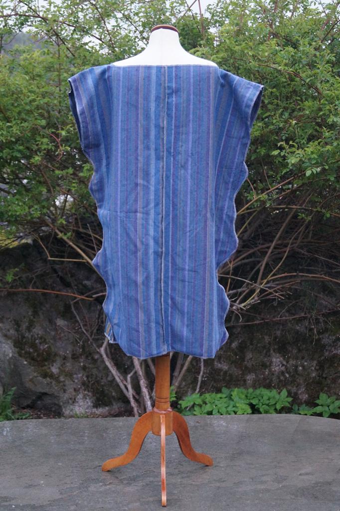 Baksiden av stripete kjole som henger på en byste.