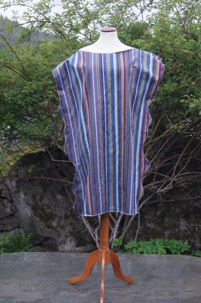 Fremsiden av stripete kjole som henger på en byste.