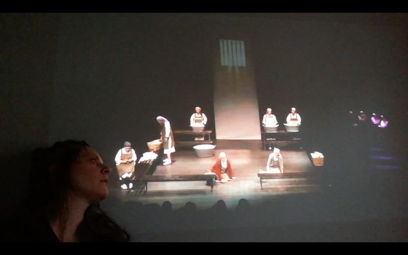 Ei scene fra en teaterforestilling projekteres mot en vegg, ei kvinne sitter nederst i venstre hjørne og ser opp på bildet som projekteres