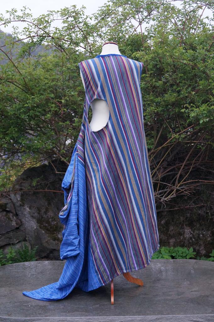 Bakside  av kjole med to ulike blåstripede stoffer som henger på en byste.