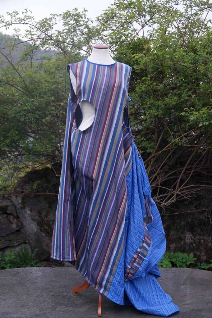 Fremsiden av kjole med to ulike blåstripede stoffer som henger på en byste.