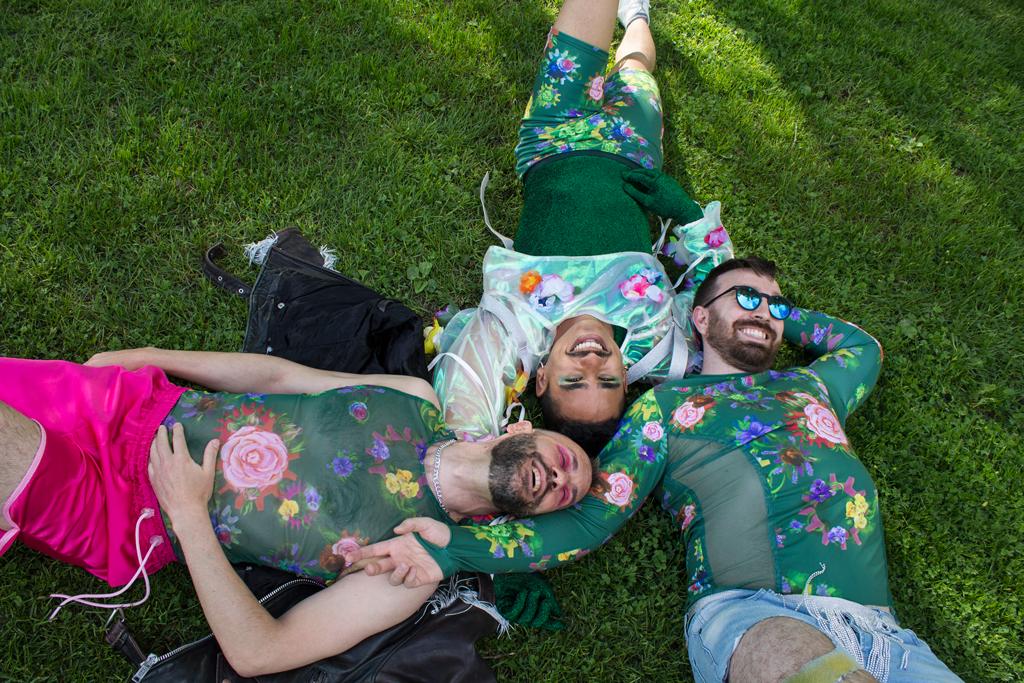 Tre menn ligger inntil hverandre på gresset og smiler. De er kledd i masterprosjektets plagg med blant annet blomsterprint.