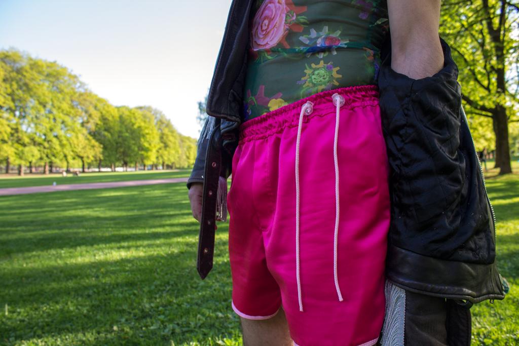 Mann i rosa shorts. Fokuset er på snørene som strammer den inn i livet.