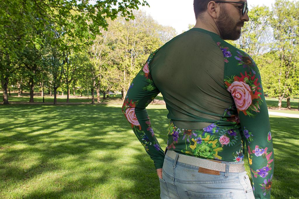 Mann i sporty genser i blomsterprint som har gjennomsiktig stoff over ryggen.