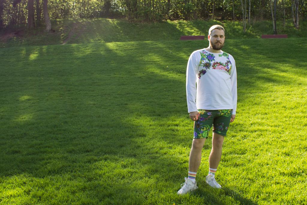 Mann som står i parken med hvit genser og blomstrete shorts.