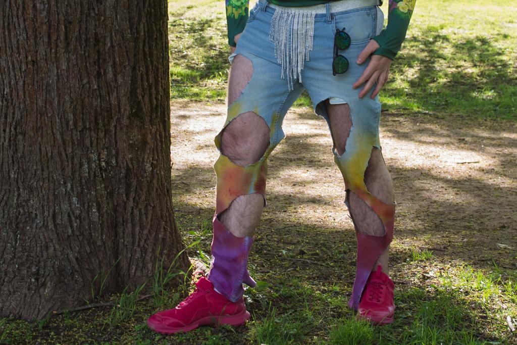 Mann ikledd hullete denimbukse som er farget fra gult til rødt til lilla nedover buksebena.