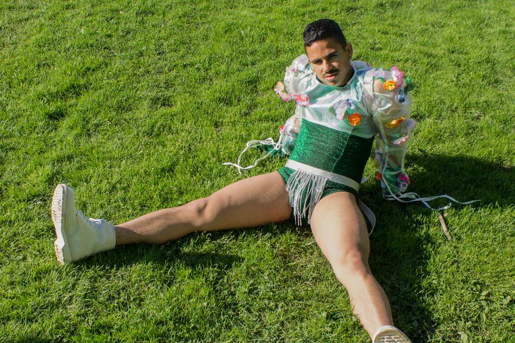 Mann sitter på gresset i glitrende og blomstrende antrekk.