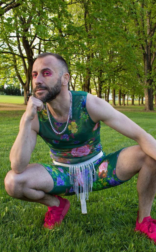Mann sitter på huk og ser inn i kamera. Han har rosa øyenskygge og grønt antrekk med blomsterprint.