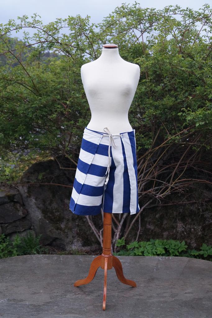 Fremsiden av en bredstripet hvit og blå shorts. Henger på en byste.