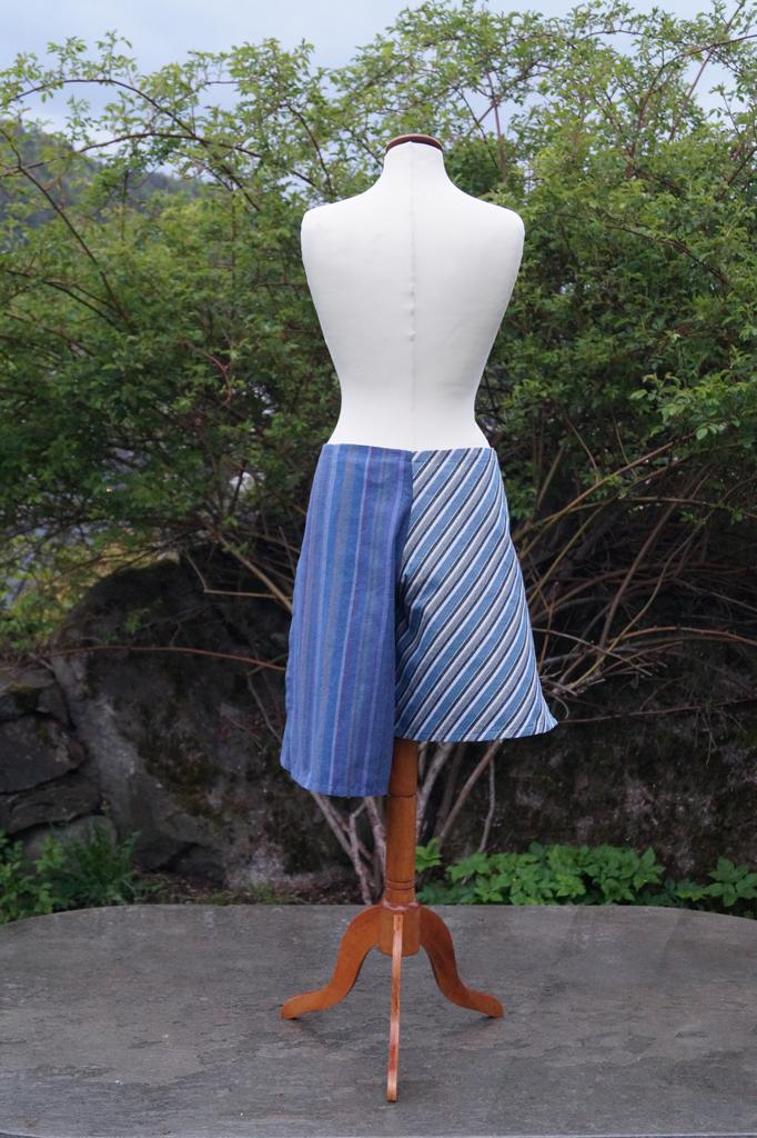Baksiden av en stripete hvit og blå knyteshort. Ulik lengde på buksebeina. Henger på en byste.