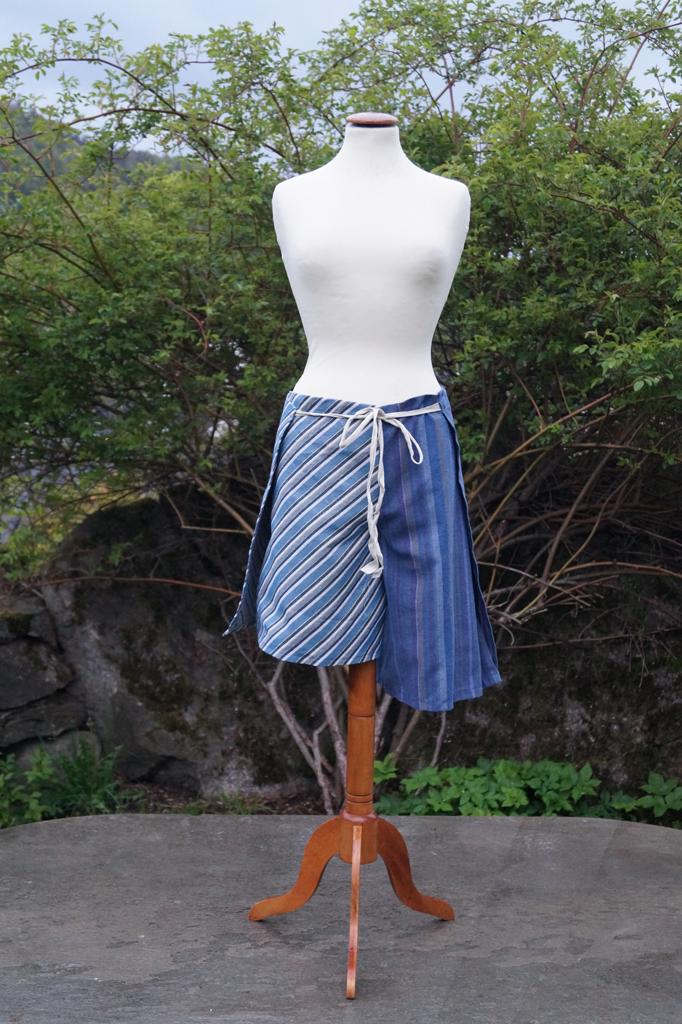 Fremsiden av en stripete hvit og blå knyteshort. Ulik lengde på buksebeina. Henger på en byste.