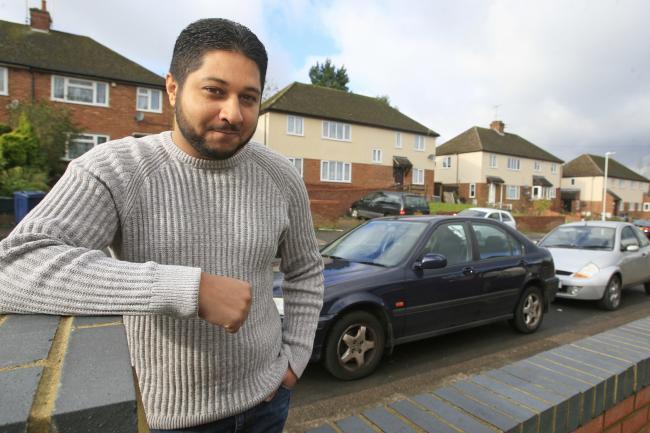 Aslam poserer smilende foran en rekke hus og biler.