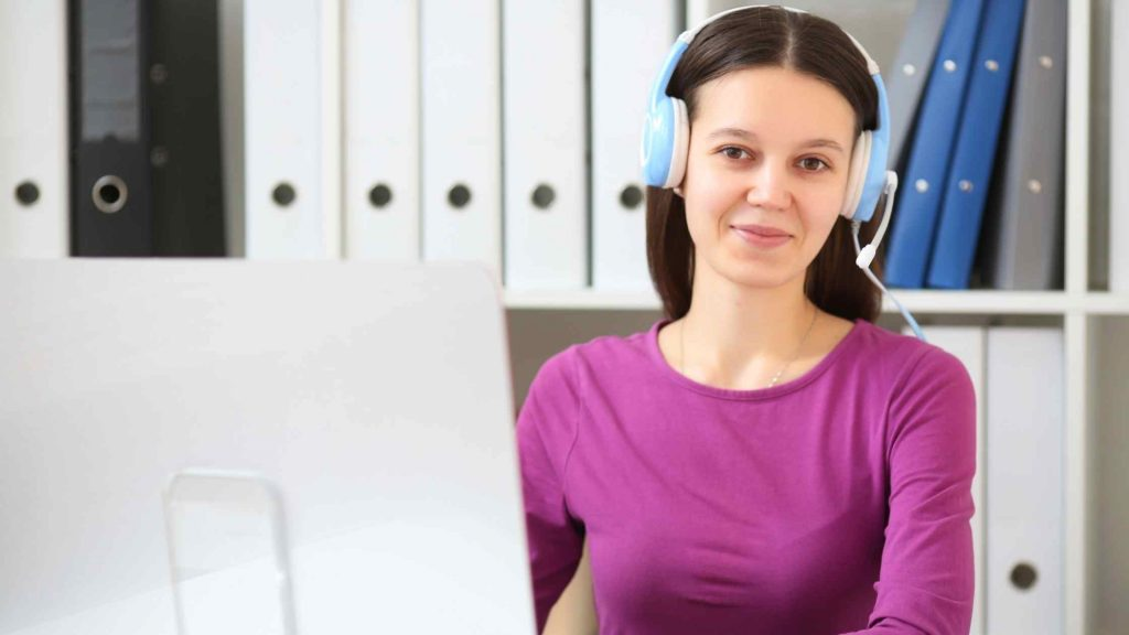 A young woman sits behind her computer wearing headphones while looking directly into the camera with a slight smile.