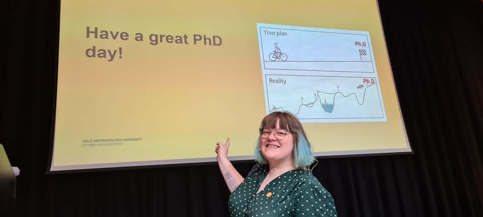 PhD forum leader Camilla Holm smiles and points at screen that reads: Have a great PhD day!