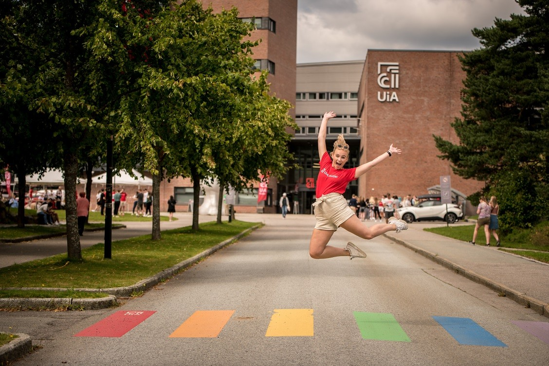 Bildet viser en student med rød UiA t-shorte som hopper foran UiA Campus Kristiansand.