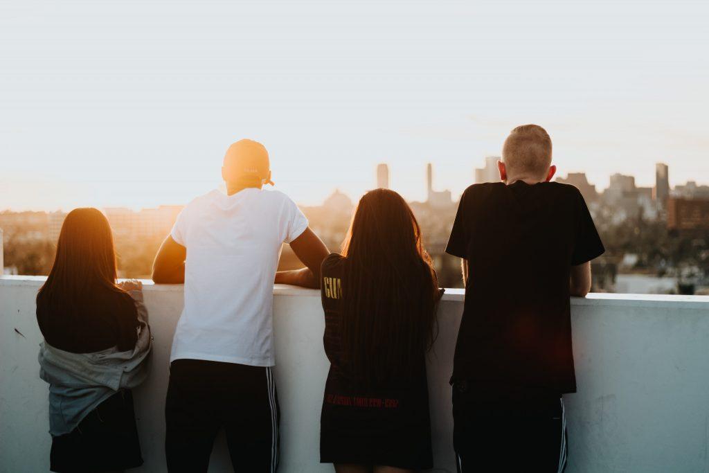Fire ungdommer står med ryggen mot kameraet og ser på utsikten
