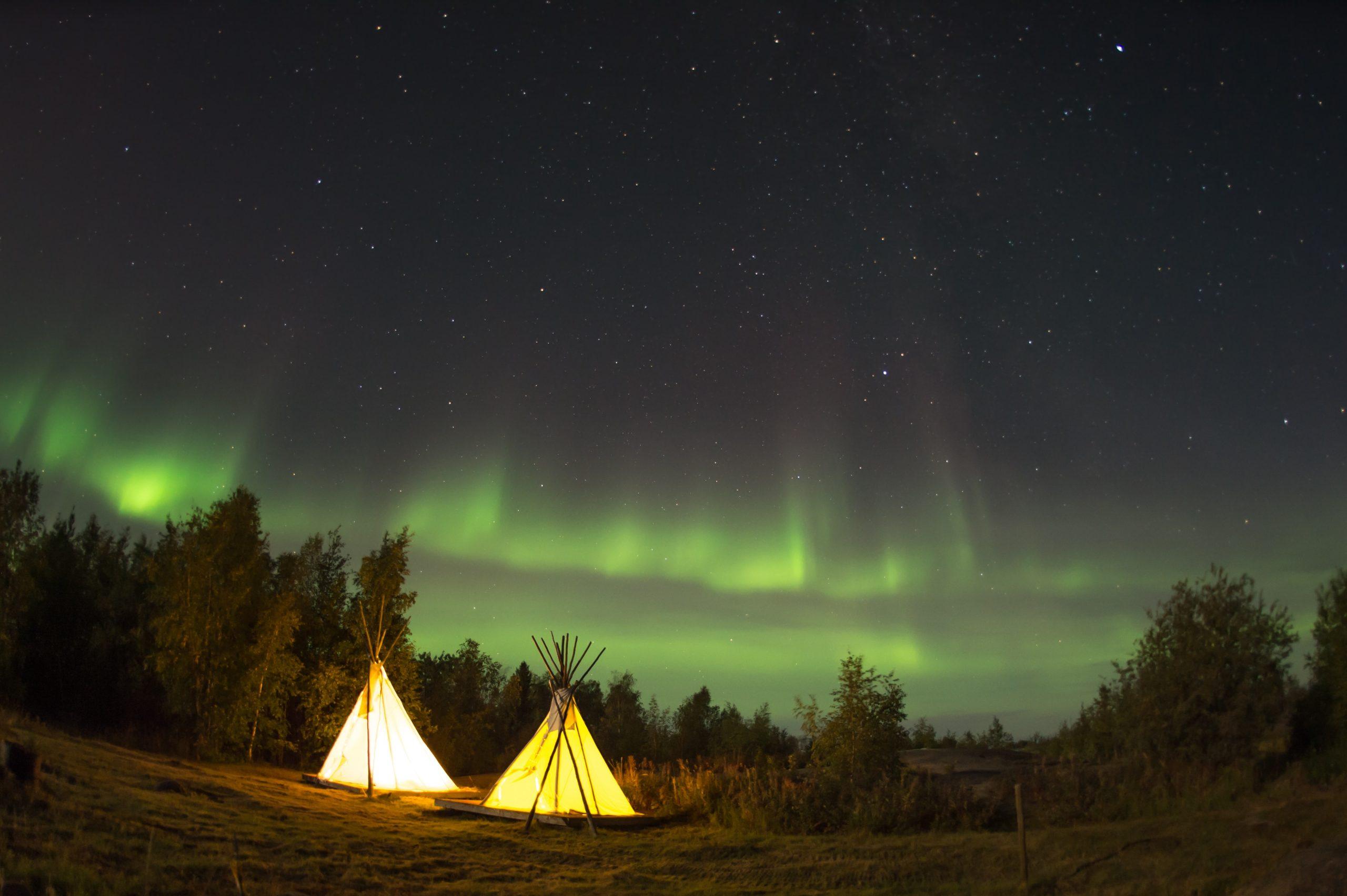 To telt i skogen på kvelden med nordlys på himmelen