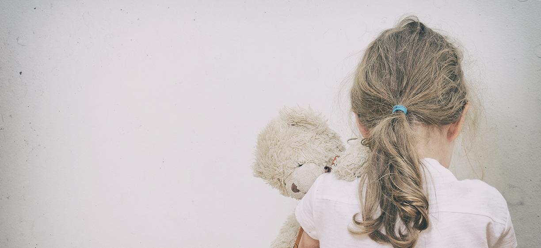 Jente med teddybjørn og ryggen til mot hvit vegg. Foto: colourbox.com