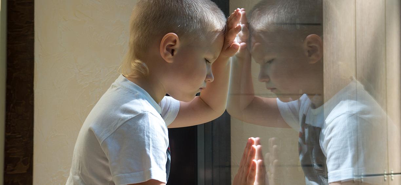 Gutt som speiler seg i vindu. Foto: colourbox.com