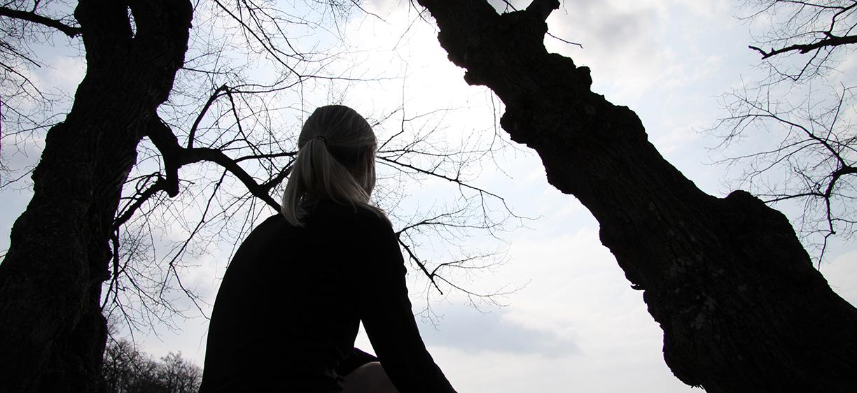 Mørk silhuett av ung kvinne mot mørke trær. colourbox.com