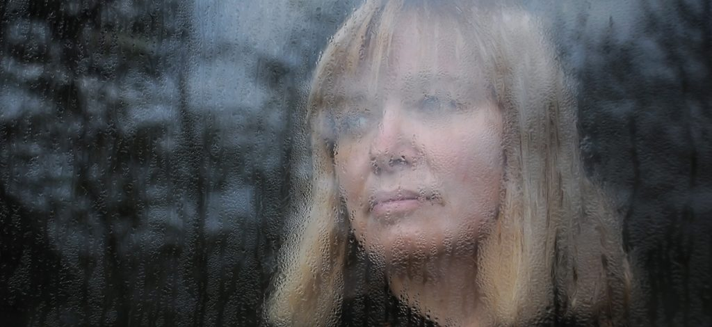 Portrait of the middle-aged woman looking through the window on a rainy day